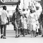 Courtesy of Don Sturkey, N.C. Collection, University of North Carolina-Chapel Hill     Two young black men pass Ku Klux Klan marchers in downtown Salisbury in August 1964.